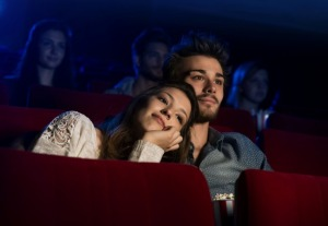Young loving couple at the cinema watching a movie, he is hugging her girlfriend