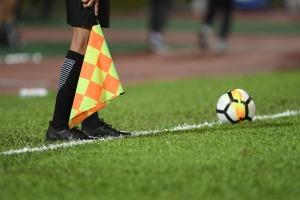 pies de arbitro auxiliar con bandera a cuadros y balon