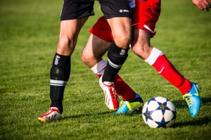 piernas de jugadores de futbol disputando un balon