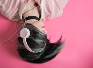 mujer con cabello en la cara audifonos rosas y fondo rosa