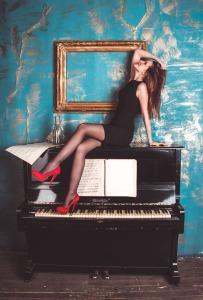 mujer de vestido negro sobre un piano